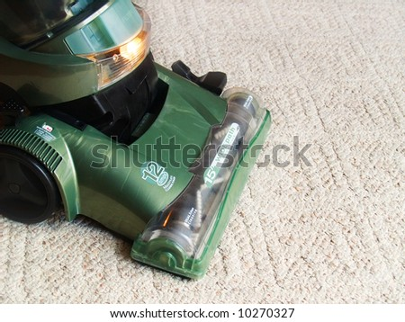 a green vacuum cleaner sweeping the carpet - stock photo