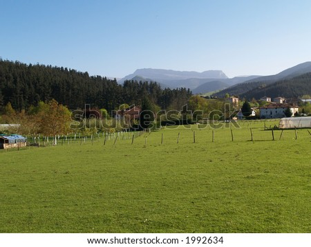 A green valley in the Basque Country, Spain. Typical basque houses and montains in the background - stock photo