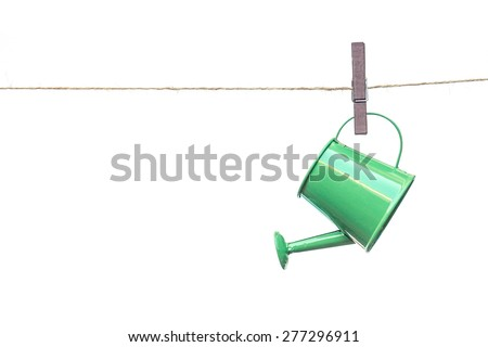 a green watering can hung on the rope with red wooden clips
