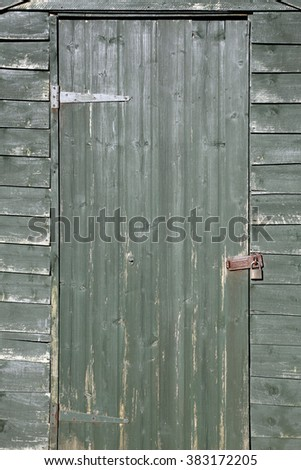 A green weathered locked shed door