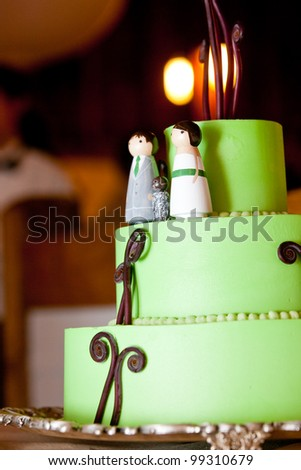 a green wedding cake with a bride and groom wedding topper - stock photo