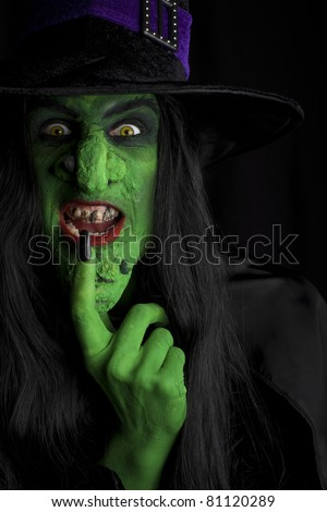 A green wicked witch, dark background. - stock photo