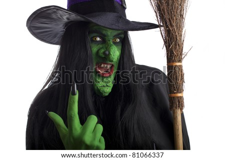 A green witch holding her broomstick and signaling come here with her finger, white background. - stock photo