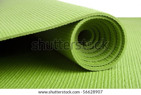 A green yoga/pilates/exercise mat rolled up on white - stock photo
