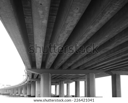 A grey bridge supported by thick concrete beams. - stock photo