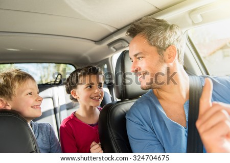 A grey hair father with beard is talking with his two kids in the car. The ten years old brother and sister are sitting in the back, they are wearing long sleeves shirts. The father have his seat belt - stock photo