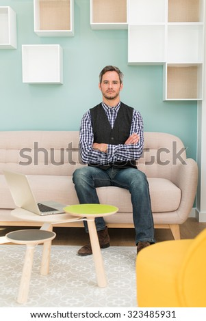 A grey hair man with beard and checkered blue shirt is sitting on a sofa in a stylish vintage waiting room with pastels colors. He is looking at camera, arms crossed, his laptop next to him - stock photo