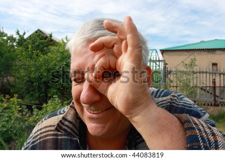 A grey-haired smiling man imitating looking through terrestrial telescope - stock photo