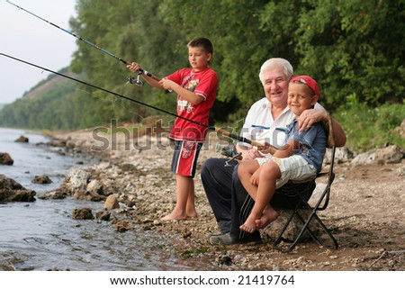 A grey-headed grandfather with a two grandsons on fishing - stock photo