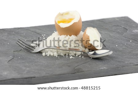 A grey slate with a soft boiled egg and sea salt. - stock photo