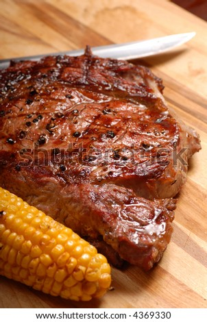 A grilled BBQ ribeye steak with corn and a knife