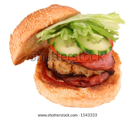 A grilled chicked pattie, bacon and fresh salad on a toasted sesame seed roll isolated with clipping path