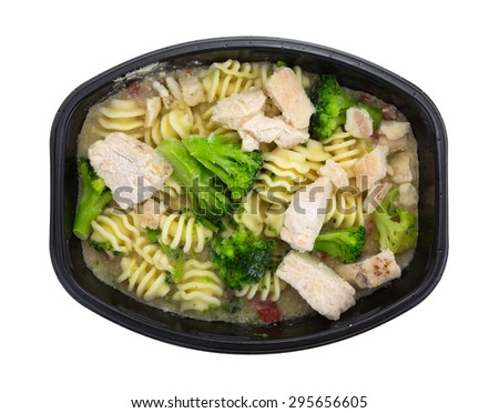 A grilled chicken with noodles and broccoli TV dinner on a white background. - stock photo