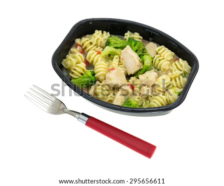 A grilled chicken with noodles and broccoli TV dinner with red handle fork on a white background. - stock photo
