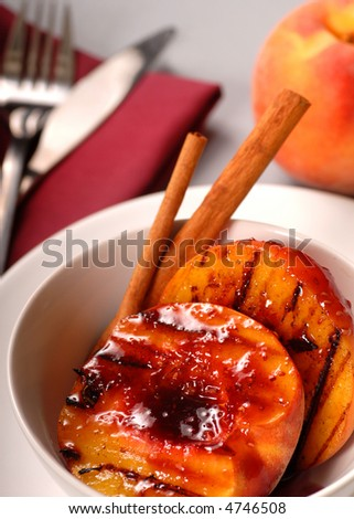 A Grilled peach with raspberry sauce, cinnamon sticks with a peach in the background - stock photo