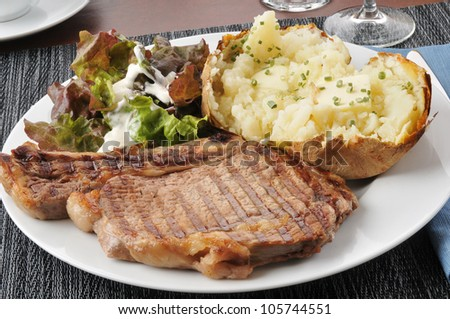 A grilled rib steak with baked potato and salad