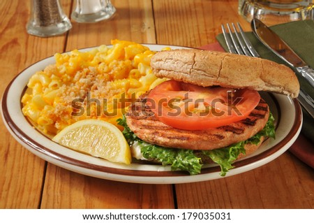 A grilled salmon burger with macaroni and cheese and beer in the background