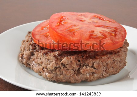 A grilled sirloin patty with sliced tomato - stock photo