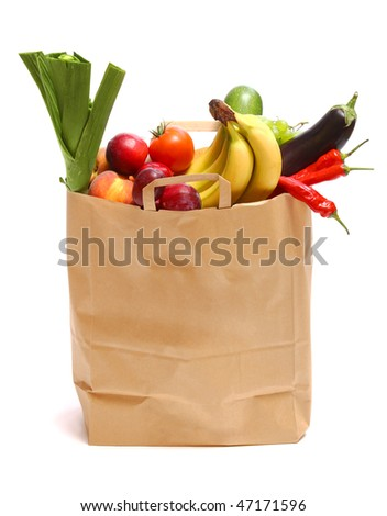 A grocery bag full of healthy fruits and vegetables on white - stock photo