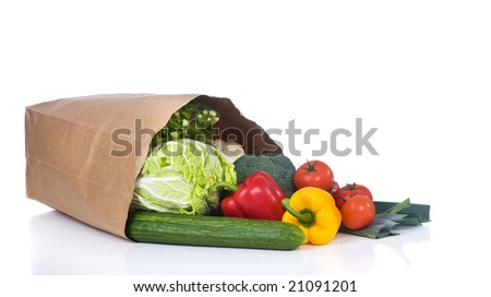 A grocery bag full of healthy vegetables and fruits.