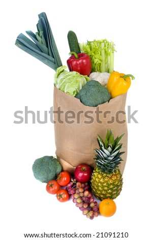 A grocery bag full of healthy vegetables and fruits. - stock photo
