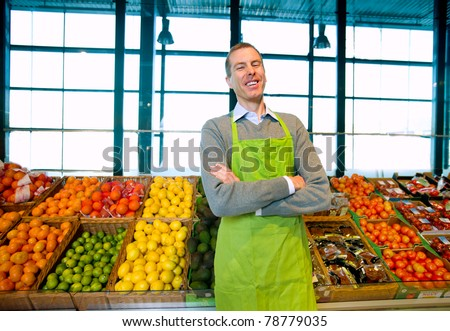 A grocery store owner standing in front of vegetables and fruit - stock photo