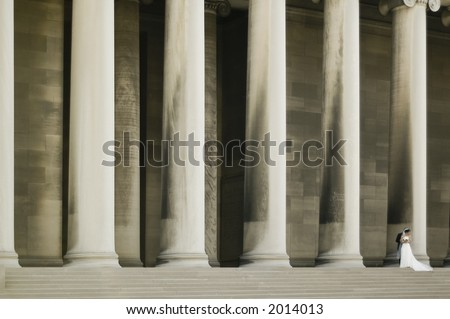 A groom embracing his bride in front of a row of enormous columns - stock photo