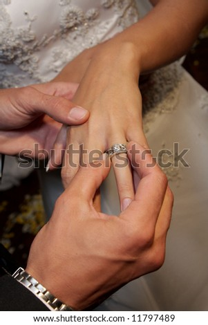 A groom giving his bride a ring - stock photo