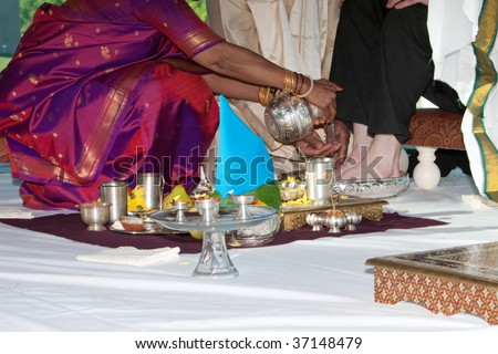 A groom has his feet washed during a traditional Hindu Indian wedding ceremony - stock photo