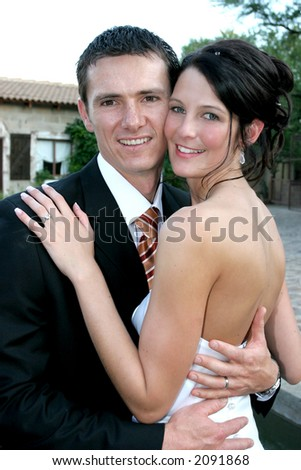 A groom holding his arms around his bride - stock photo