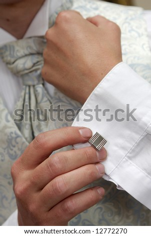 A groom putting on his cuflings - stock photo