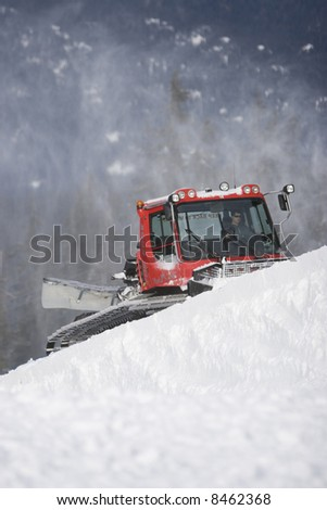 A grooming machine sculpts a ski run by pushing fresh snow