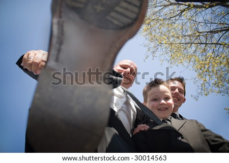 A groomsman in a wedding party decides to stomp on the photographer.  This could be used for a variety of concepts. - stock photo