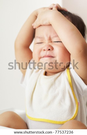 A grouchy baby expressing frustration or discomfort with arms over head. - stock photo