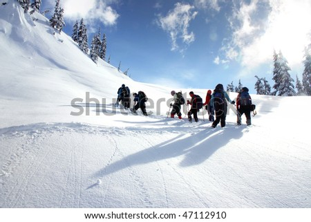 A group hikers are snowshoeing on snow mountain in BC, Canada. - stock photo