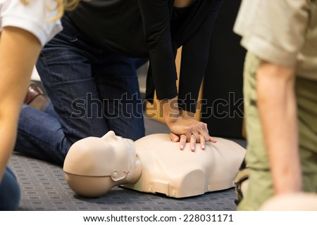 A group of adult education students practitcing CPR chest compressioon on a dummy.  - stock photo
