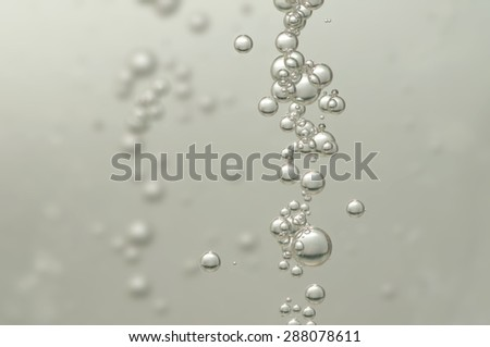 A group of air bubbles rising in a glass of wine - stock photo