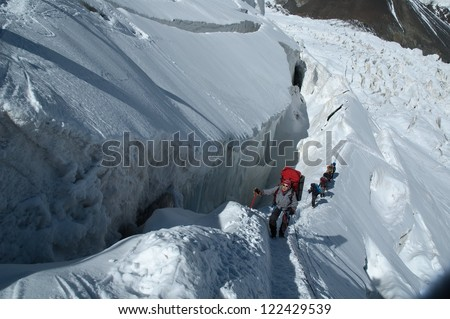 A group of alpine hikers climbing along a big crevasse on their way up to Lenin peak summit.