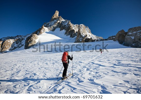 A group of backcountry skiers walks up to the Dent du Geant, Mont Blanc massif, Chamonix, west Alps, France, Europe.