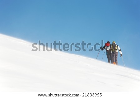 A group of backcountry skiers walks up to the top of the mountain in the blizzard, italian alps, europe.