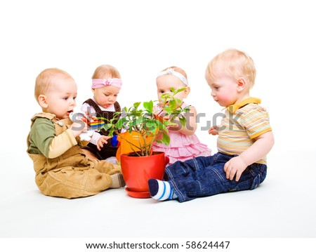 A group of beautiful babies sitting around a potted plant - stock photo