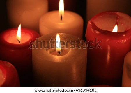 A group of burning candles, red and white