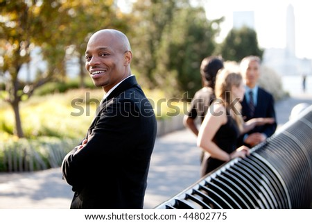 A group of business colleagues in the park - focus on front man - stock photo