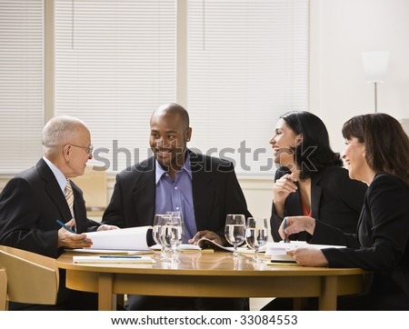 A group of business people are in a meeting in an office.  They are talking and laughing and looking away from the camera.  Horizontally framed shot. - stock photo
