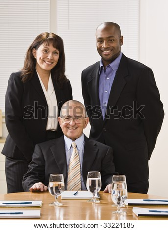 A group of business people are in an office and are smiling at the camera.  Vertically framed shot.