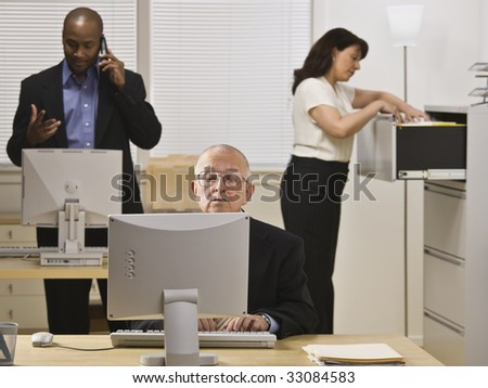 A group of business people are working in an office.  Horizontally framed shot.
