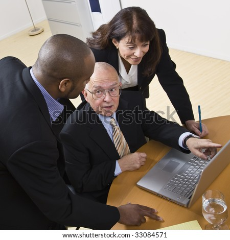 A group of business people are working on a laptop.  The elderly man is speaking to and looking at the younger man, and the young woman is looking at the computer screen.  Square framed shot. - stock photo