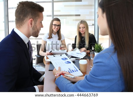 A group of business people at a meeting on the background of office. Focus on a beautiful brunette