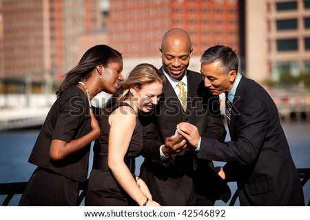 A group of business people crowded around a cell phone - stock photo