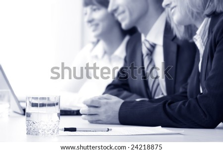 A group of business people. Focus on a glass with water - stock photo
